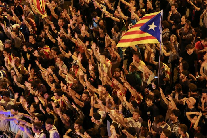 People raise arms and shout during a demonstration two days after the banned independence referendum in Barcelona, Spain, Oct