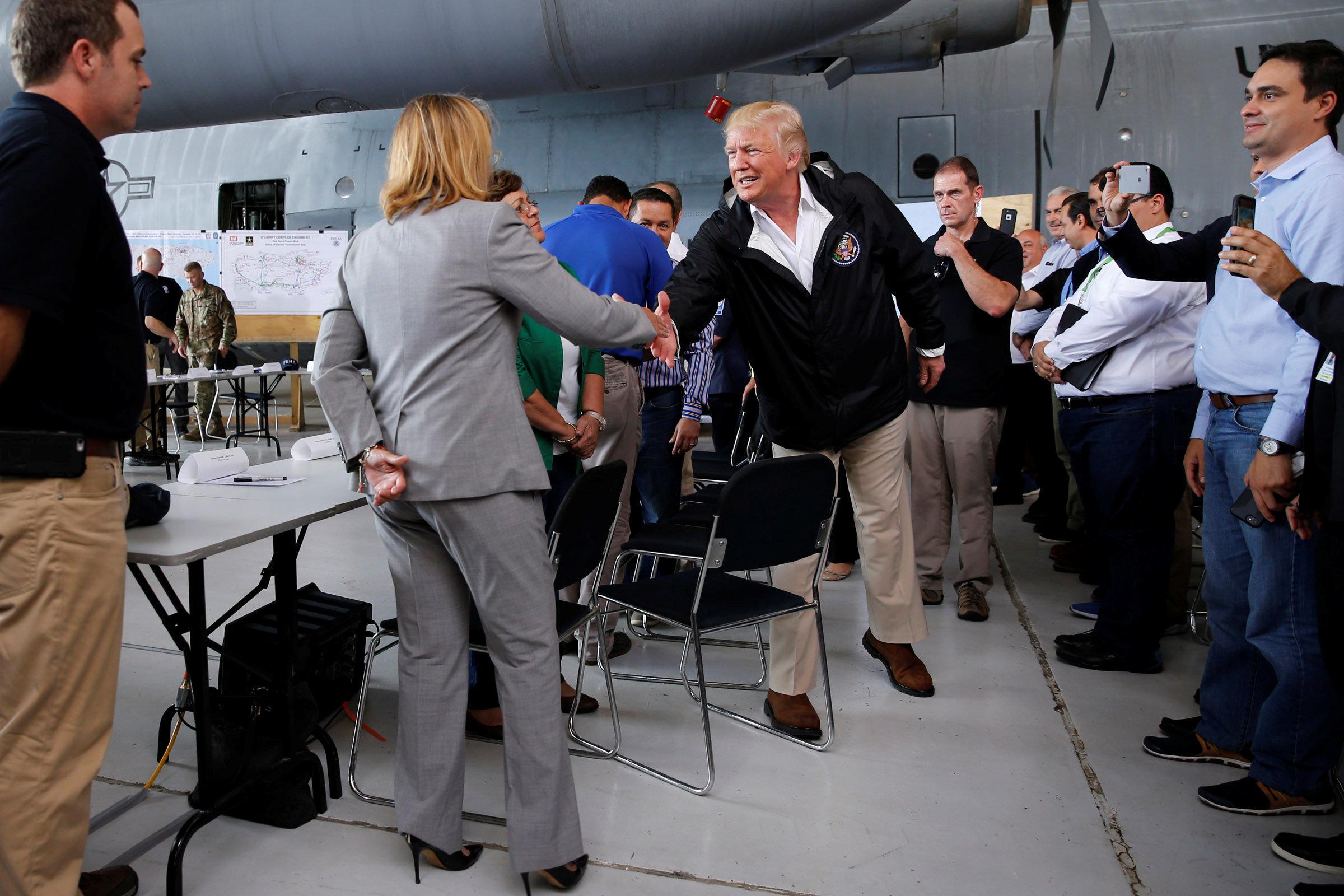 U.S. President Donald Trump shakes hands with San Juan Mayor Carmen Yulin Cruz before a briefing to survey hurricane damage, at Muniz Air National Guard Base in Carolina, Puerto Rico, U.S. October 3, 2017. REUTERS/Jonathan Ernst