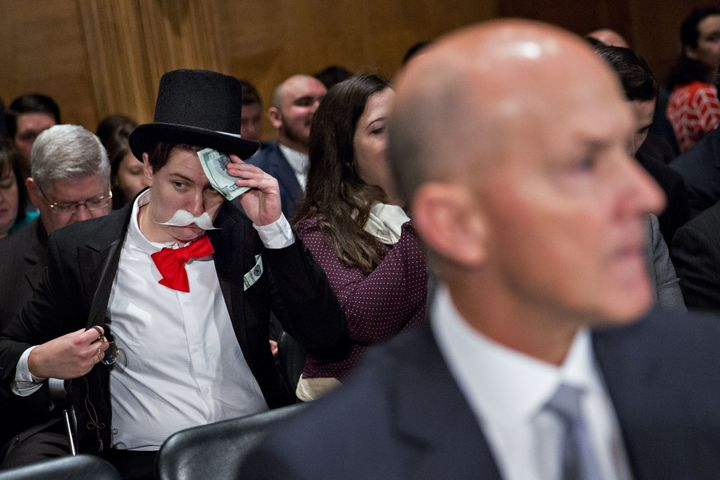 A demonstrator sits in costume behind Richard Smith, former chairman and chief executive officer of Equifax Inc., right, befo