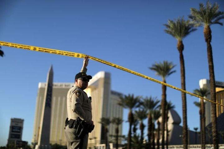 A police officer stands in front of the closed Las Vegas Strip next to the site of the Route 91 music festival mass shooting
