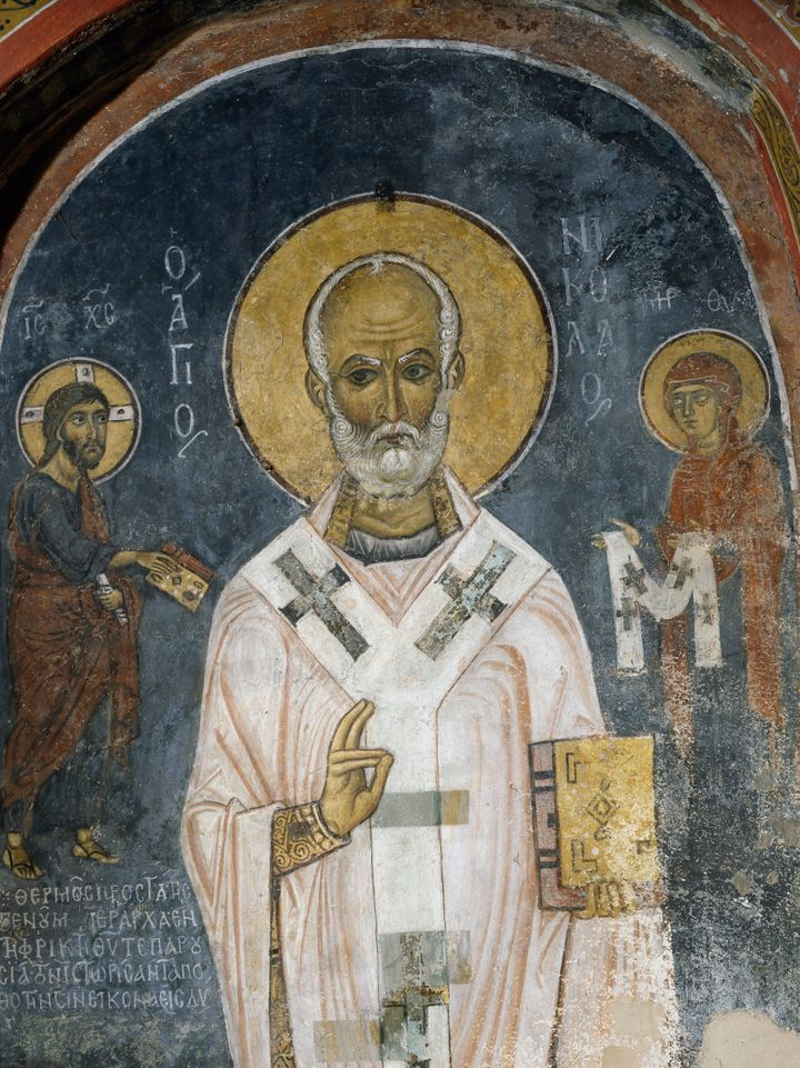 St. Nicholas of Myra is seen in this 12th-century fresco. The saint's acts of generosity, particularly to children, inspired the red and white-suited figure known as Santa Claus.