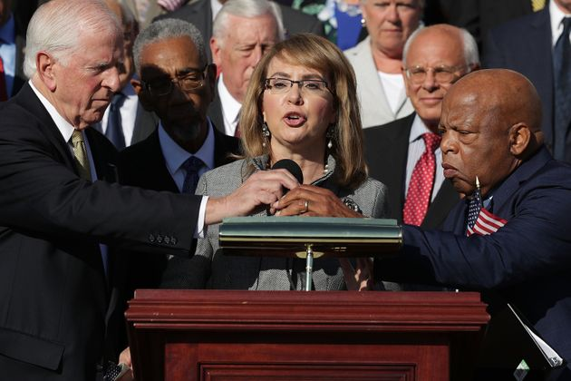 Gabby Giffords, who was serving in Congress when she was shot in 2011, addresses a rally with fellow...