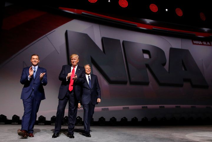 NRA Executive Director Chris Cox, left, and Executive Vice President and CEO Wayne LaPierre, right, welcome President Donald