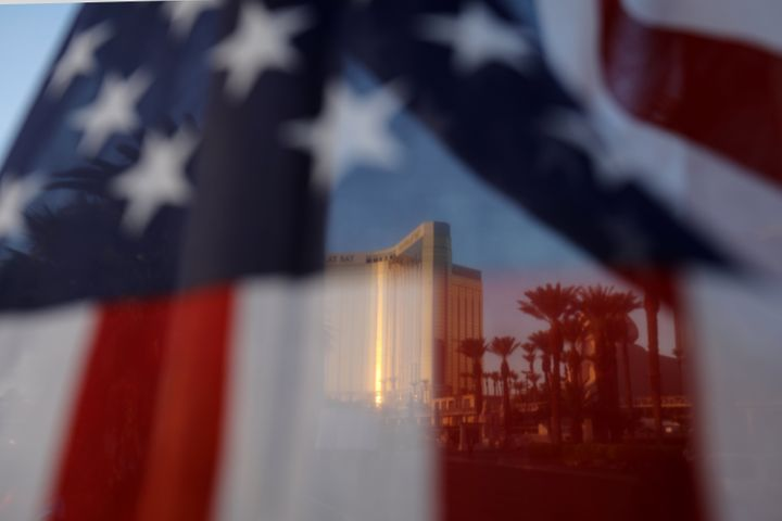 The Mandalay Bay hotel is shown through an American flag blowing in the wind at a memorial next to the mass shooting site alo