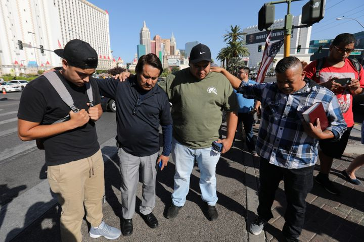 A group of men pray at a makeshift memorial in the middle of Las Vegas Boulevard following the mass shooting in Las Vegas, Ne
