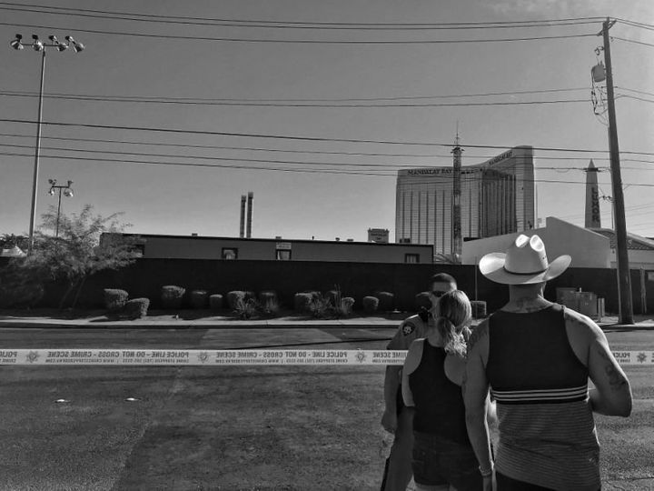A couple speaks to a Las Vegas police officer guarding the perimeter of the Route 91 festival site Monday in Las Vegas.