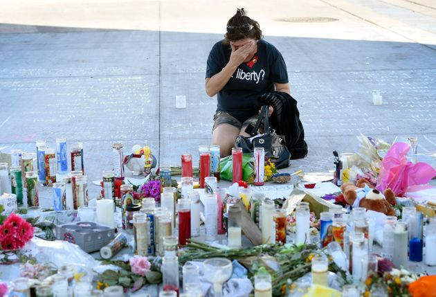 A woman wipes her eyes at a memorial on Las Vegas strip to those who