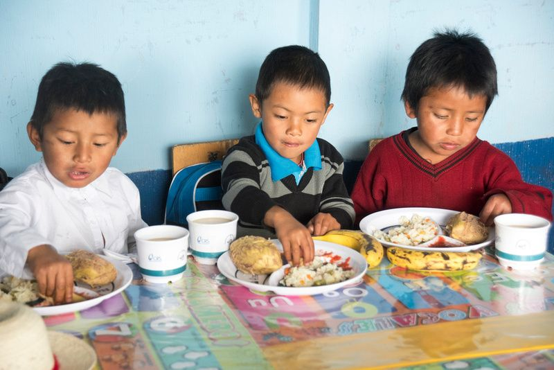 Students of the Paronchaj primary school in Totonicapán, Guatemala,  enjoy a school lunch made possible by USDA through CRS