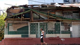 A pedestrian passes in front of a home damaged after Hurricane Maria in San Juan, Puerto Rico, on Friday, Sept. 29, 2017. Trump defended his administration's handling of the crisis in Puerto Rico following Hurricane Maria, saying the federal government is fully engaged in responding to storm damage of 'historic and catastrophic severity.' Photographer: Alex Wroblewski/Bloomberg via Getty Images