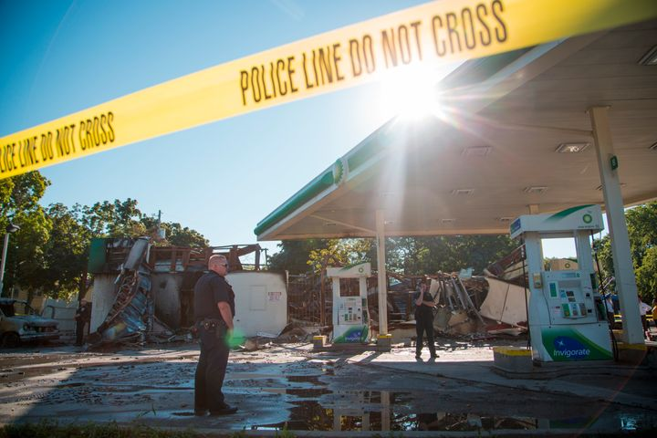 MILWAUKEE, WI - AUGUST 14: A police officer stands guard in front of the damage to the BP gas station after rioters clashed w