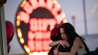 LAS VEGAS, NV - OCTOBER 4: Las Vegas resident Elisabeth Apcar (R) hugs a woman who was working at the concert venue on Sunday night (she wished to remain anonymous), at a makeshift memorial at the northern end of the Last Vegas Strip, October 4, 2017 in Las Vegas, Nevada. On October 1, Stephen Paddock killed at least 58 people and injured more than 450 after he opened fire on a large crowd at the Route 91 Harvest country music festival. The massacre is one of the deadliest mass shooting events in U.S. history. (Photo by Drew Angerer/Getty Images)