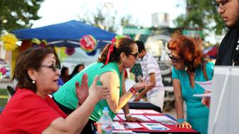 University of Arizona Center for Rural Health Navigators Maria Losoya (L) and Gabriela Campos de Marcorin give people information and answer questions about health insurance at the Celebracion de la Independencia de Mexico in Tucson, Arizona, U.S. September 16, 2017.  Photo taken September 16, 2017.     REUTERS/Caitlin O'Hara
