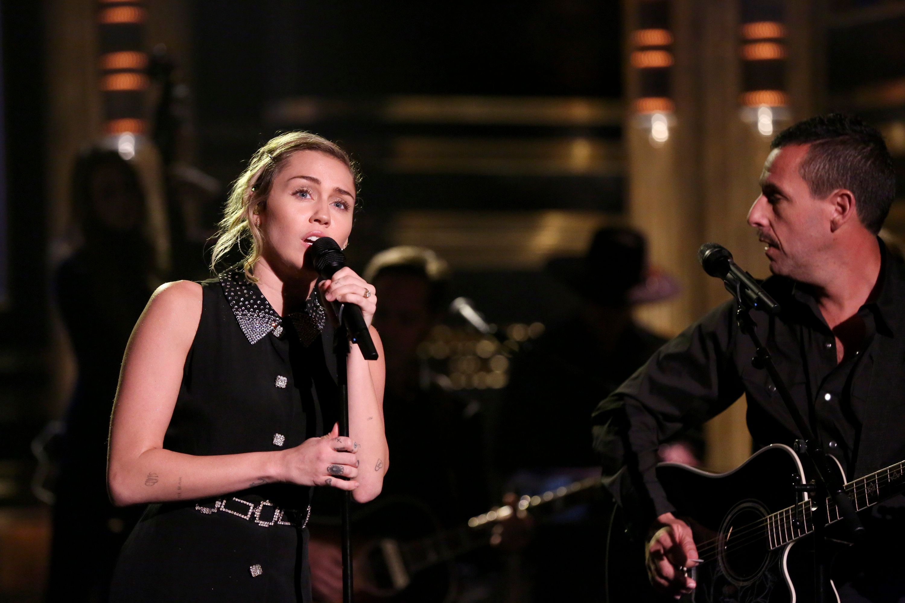 THE TONIGHT SHOW STARRING JIMMY FALLON -- Episode 0749 -- Pictured: (l-r) Singer/Songwriter Miley Cyrus and Actor Adam Sandler perform 'No Freedom' on October 2, 2017 -- (Photo by: Andrew Lipovsky/NBC/NBCU Photo Bank via Getty Images)