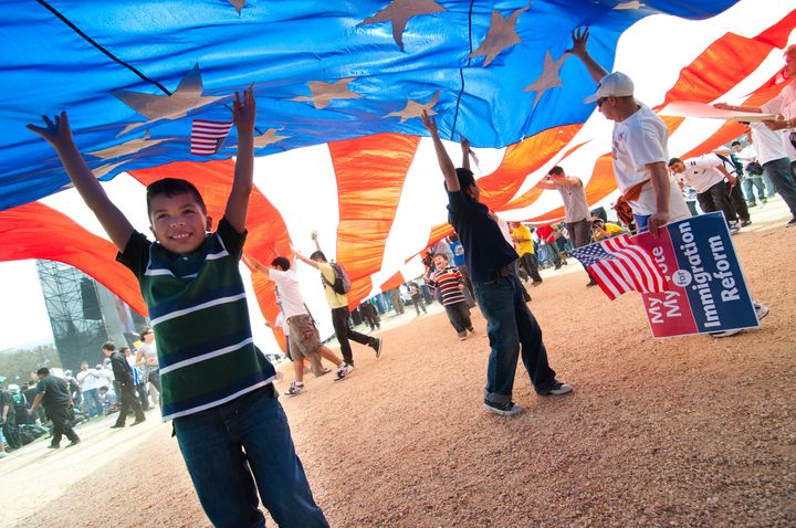 Washington, DC, USA - March 21, 2010: Children play under a giant American flag as some 200,000 immigrants' rights activi