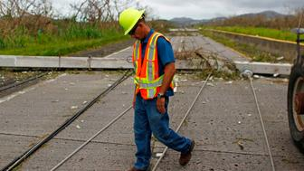 A Puerto Rico Power Authority worker walks between downed power lines in the aftermath of Hurricane Maria in Luquillo, Puerto Rico, Thursday, September 21, 2017. Puerto Rico braced for potentially calamitous flash flooding after being pummeled by Hurricane Maria which devastated the island and knocked out the entire electricity grid. The hurricane, which Puerto Rico Governor Ricardo Rossello called 'the most devastating storm in a century,' had battered the island of 3.4 million people after roaring ashore early Wednesday with deadly winds and heavy rain.  / AFP PHOTO / Ricardo ARDUENGO        (Photo credit should read RICARDO ARDUENGO/AFP/Getty Images)