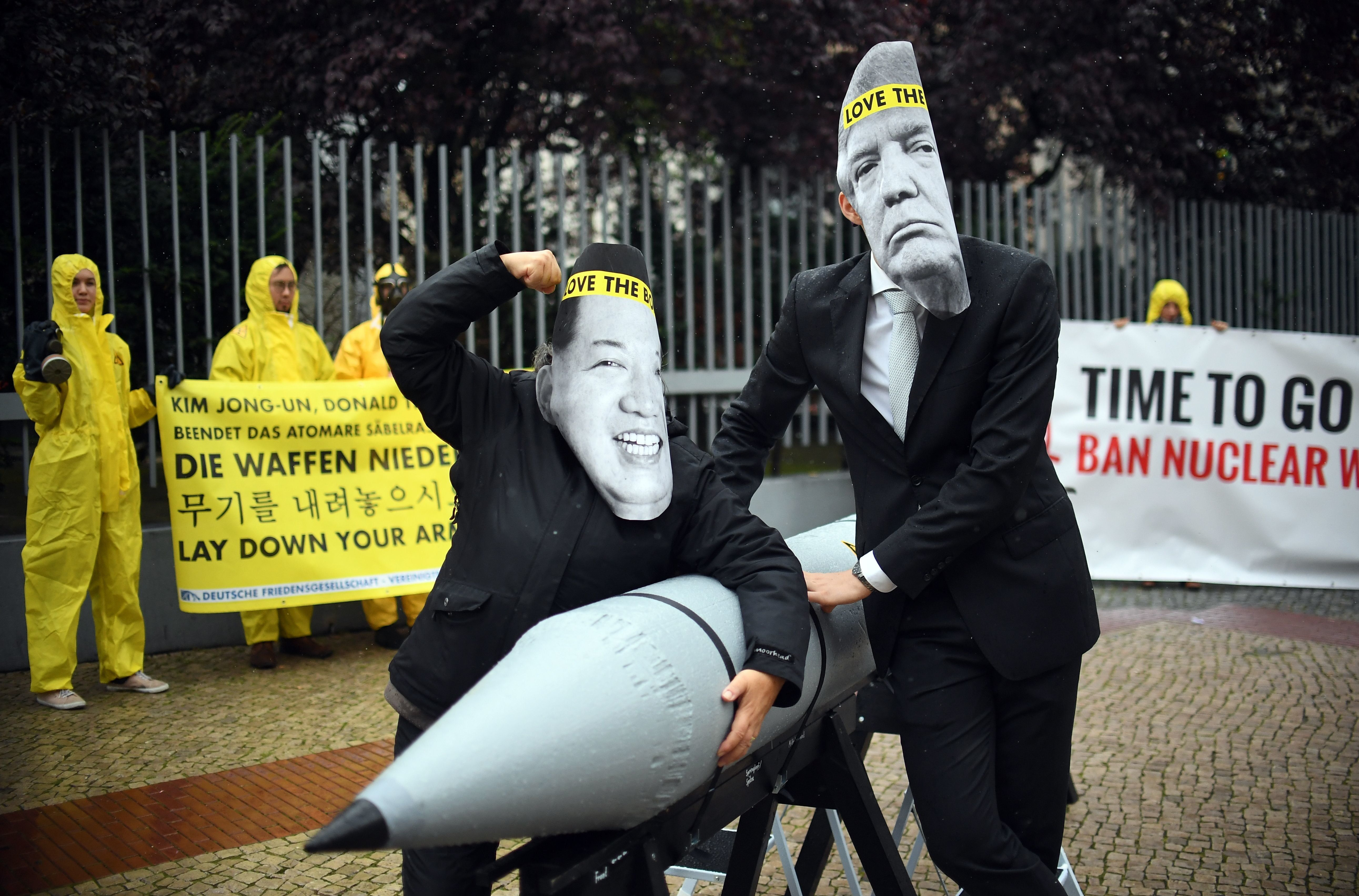 Activists of the non-governmental organization 'International Campaign to Abolish Nuclear Weapons (ICAN)' wear masks of US President Donal Trump and leader of the Democratic People's Republic of Korea Kim Jon-un while posing with a mock missile in front of the embassy of Democratic People's Republic of Korea in Berlin, on September 13, 2017. / AFP PHOTO / dpa / Britta Pedersen / Germany OUT        (Photo credit should read BRITTA PEDERSEN/AFP/Getty Images)