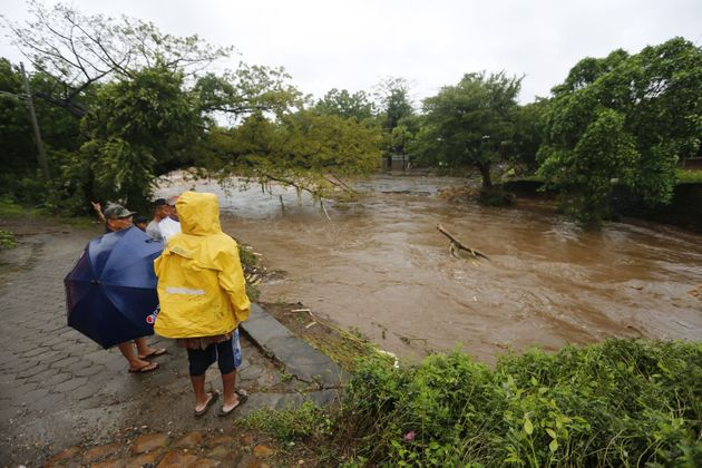 Residents watch the swollen floodwaters of the river