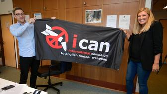 Nuclear disarmament group ICAN executive director Beatrice Fihn (R) and coordinator Daniel Hogstan hold a banner with their logo after ICAN won the Nobel Peace Prize for its decade-long campaign to rid the world of the atomic bomb as nuclear-fuelled crises swirl over North Korea and Iran, on October 6, 2017 in Geneva. With the nuclear threat at its most acute in decades, the International Campaign to Abolish Nuclear Weapons, which on October 6 won the Nobel Peace Prize, is urgently pressing to consign the bomb to history. / AFP PHOTO / Fabrice COFFRINI        (Photo credit should read FABRICE COFFRINI/AFP/Getty Images)