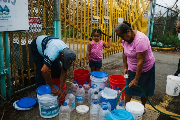 Residents fill containers with water at a center in Rio Grande, Puerto Rico, on Tuesday, Oct. 3, 2017.