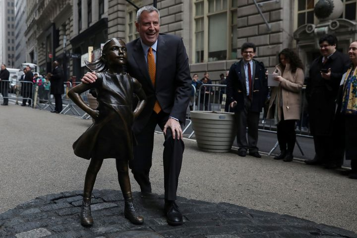 New York City Mayor Bill de Blasio poses next to the Fearless Girl statue in New York on March 27, 2017.