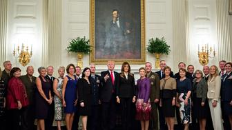WASHINGTON, DC - OCTOBER 5:  U.S. President Donald Trump and first lady Melania Trump pose for pictures with senior military leaders and spouses after a briefing in the State Dining Room of the White House October 5, 2017 in Washington, D.C. The Trumps are hosting the group for a dinner in the Blue Room.  (Photo by Andrew Harrer-Pool/Getty Images)