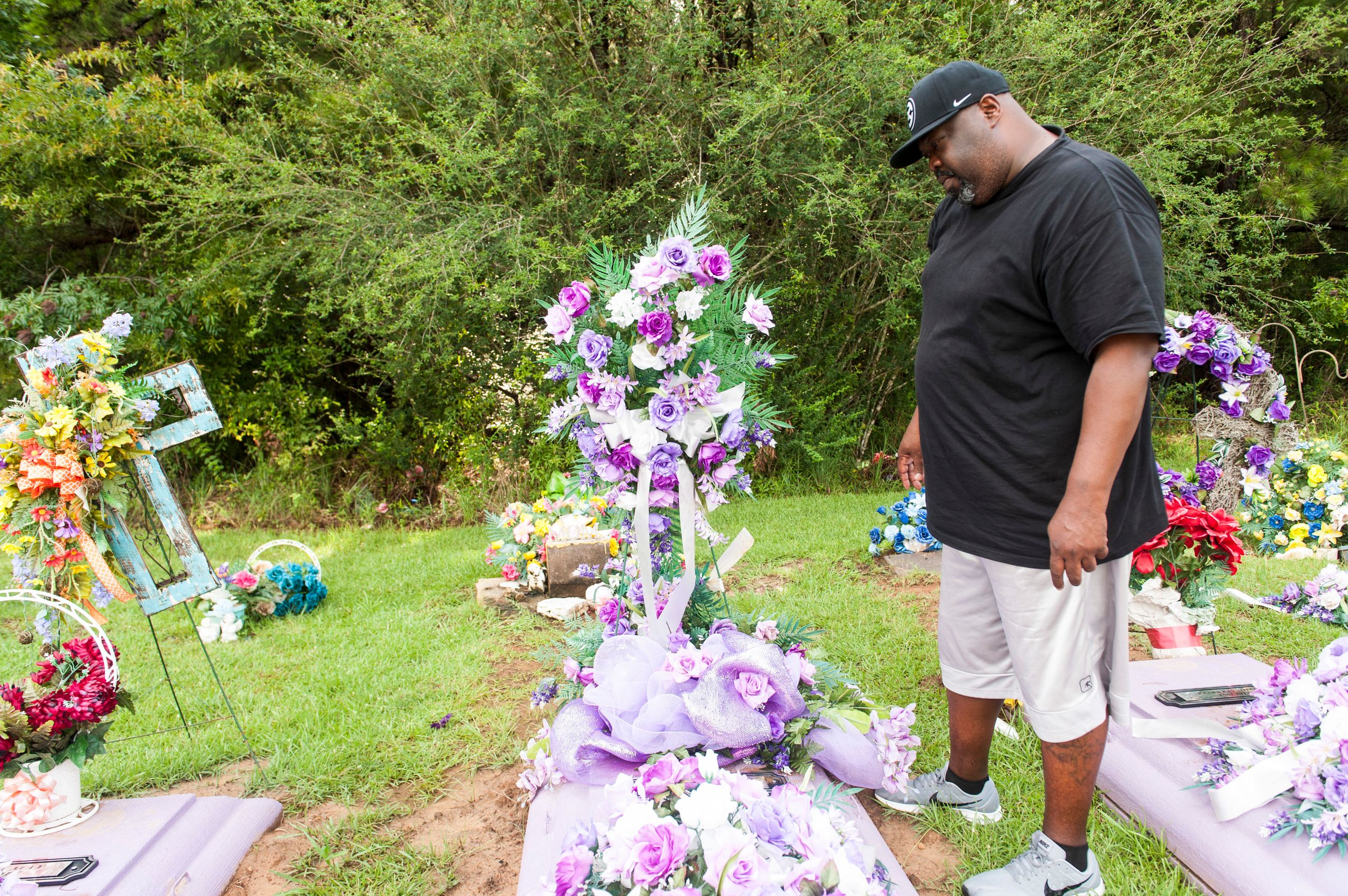 Vincent Mitchell looks at his wife's grave at a cemetery in Bogue Chitto.
