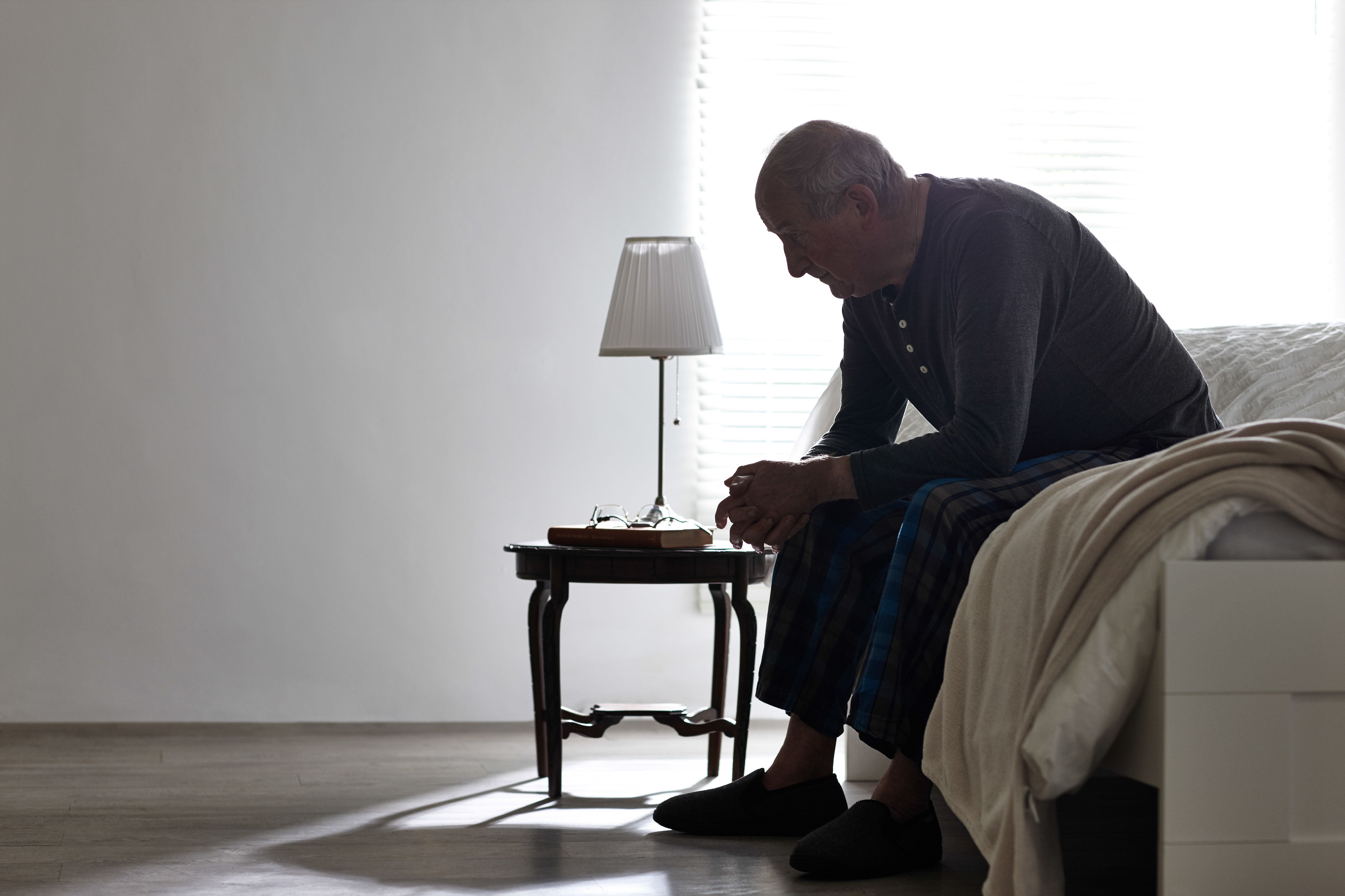 Elderly man sitting on bed looking serious - Indoors