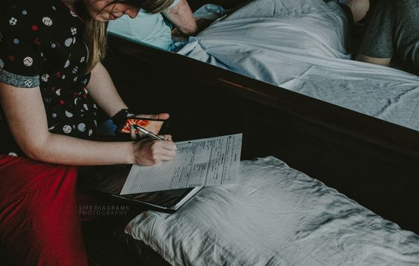 """""""This midwife is timing contractions and taking notes during a home birth."""""""