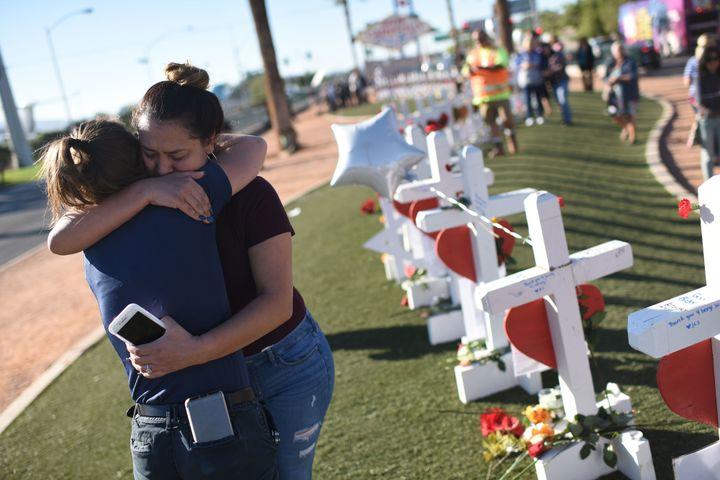 Melissa Gerber (L) and Sandra Serralde (R) comfort each other beside 58 white crosses.