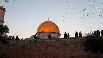 Palestinians sit on a wall overlooking the Dome of Rock mosque inside the Al-Aqsa Mosque compound, Islam's third holiest site, following the morning Eid al-Adha prayer in Jerusalem's Old City on on September 1, 2017. Eid al-Adha (the Festival of Sacrifice) is celebrated throughout the Muslim world as a commemoration of Abraham's willingness to sacrifice his son for God, and cows, camels, goats and sheep are traditionally slaughtered on the holiest day. / AFP PHOTO / AHMAD GHARABLI        (Photo credit should read AHMAD GHARABLI/AFP/Getty Images)