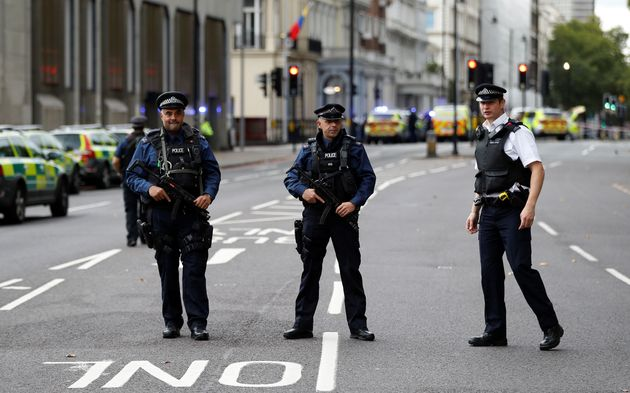 Police officers stand in the road outside the Natural History