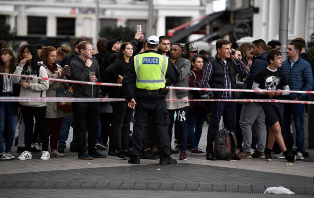 A police officer stands at a cordoned off area near the