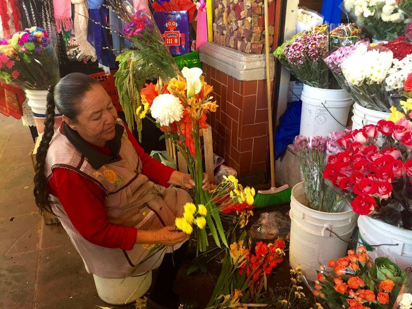 A woman assembles a bouquet at Mercado San Angel.