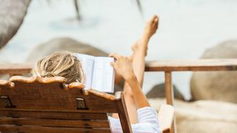 Young woman reading a book while relaxing on tropical island. Koh Phangan island, Thailand
