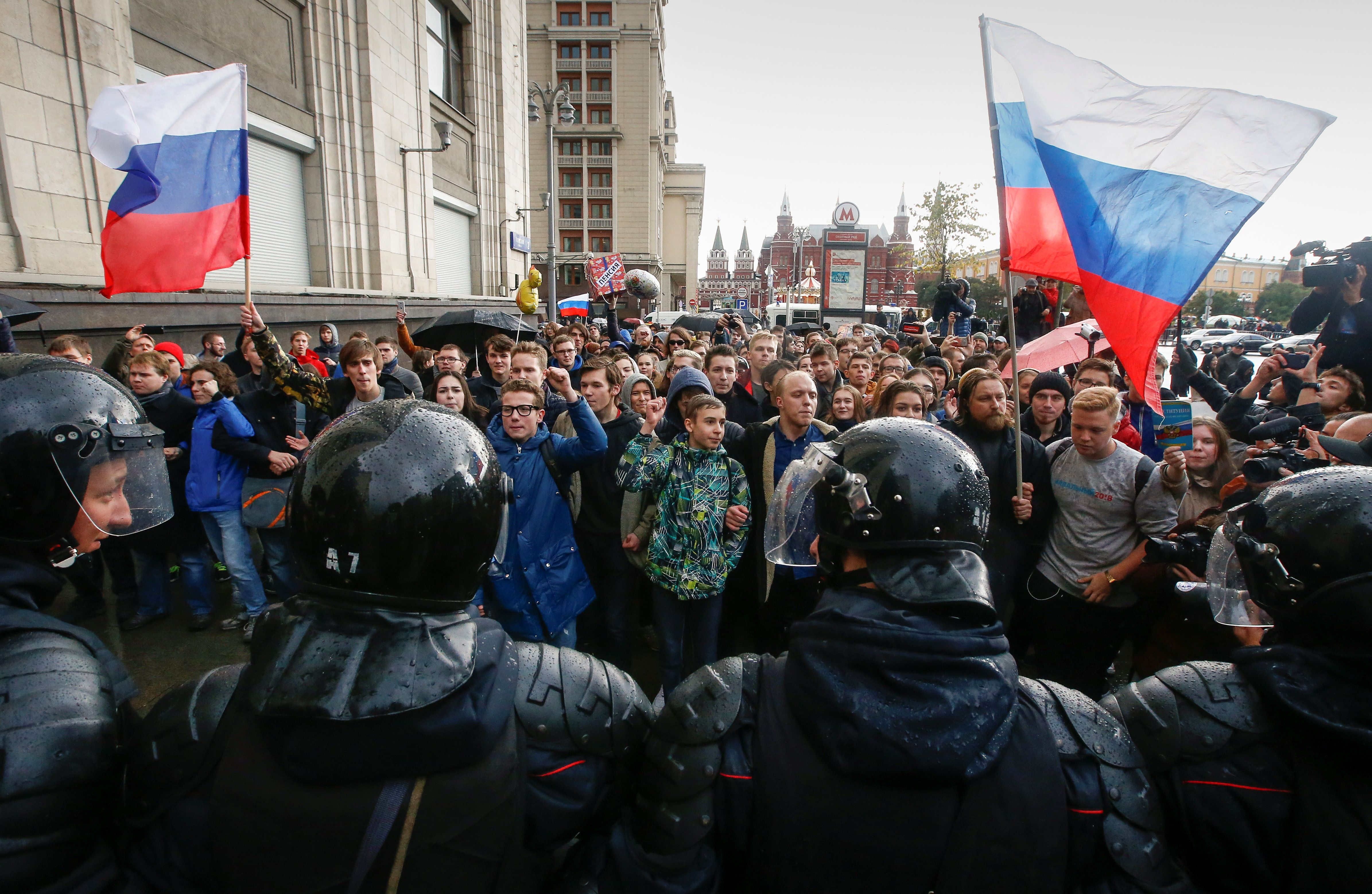 Police officers block supporters of Russian opposition leader Alexei Navalny during a rally in Moscow, Russia October 7, 2017
