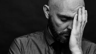 Depressed man covering face with hand