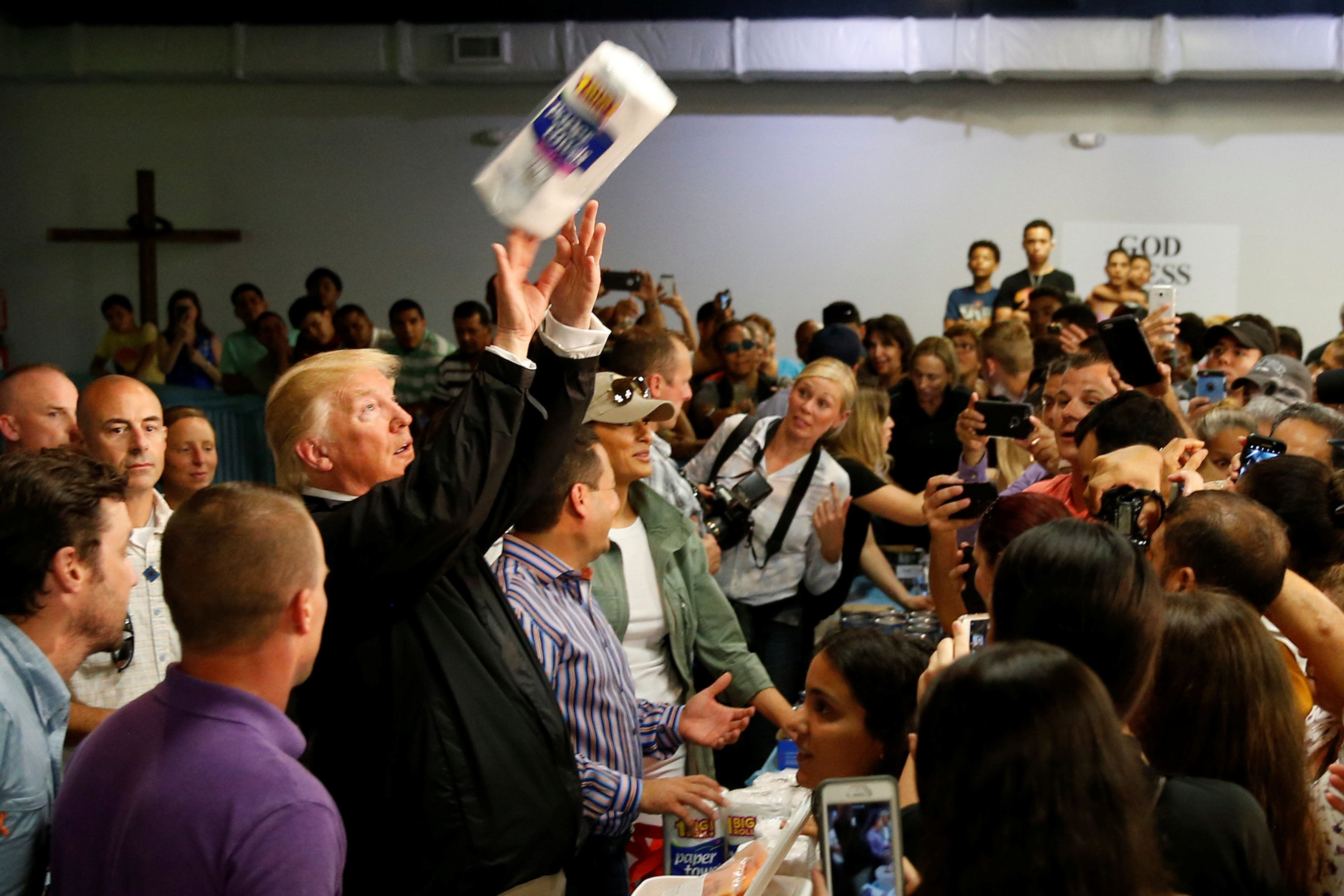 U.S. President Donald Trump tosses rolls of paper towels to people at a hurricane relief distribution center at Calvary Chapel in San Juan, Puerto Rico, October 3, 2017. REUTERS/Jonathan Ernst