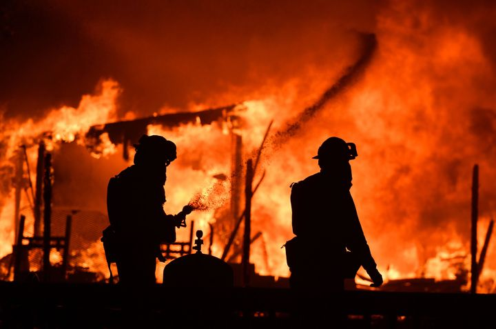 Firefighters douse flames as a home burns in the Napa wine region in California on October 9, 2017, as multiple wind-driven f