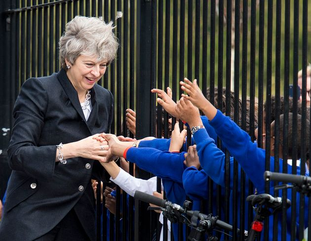 Theresa May is greeted by primary pupils during a visit to the Dunraven School in Streatham, south London,...