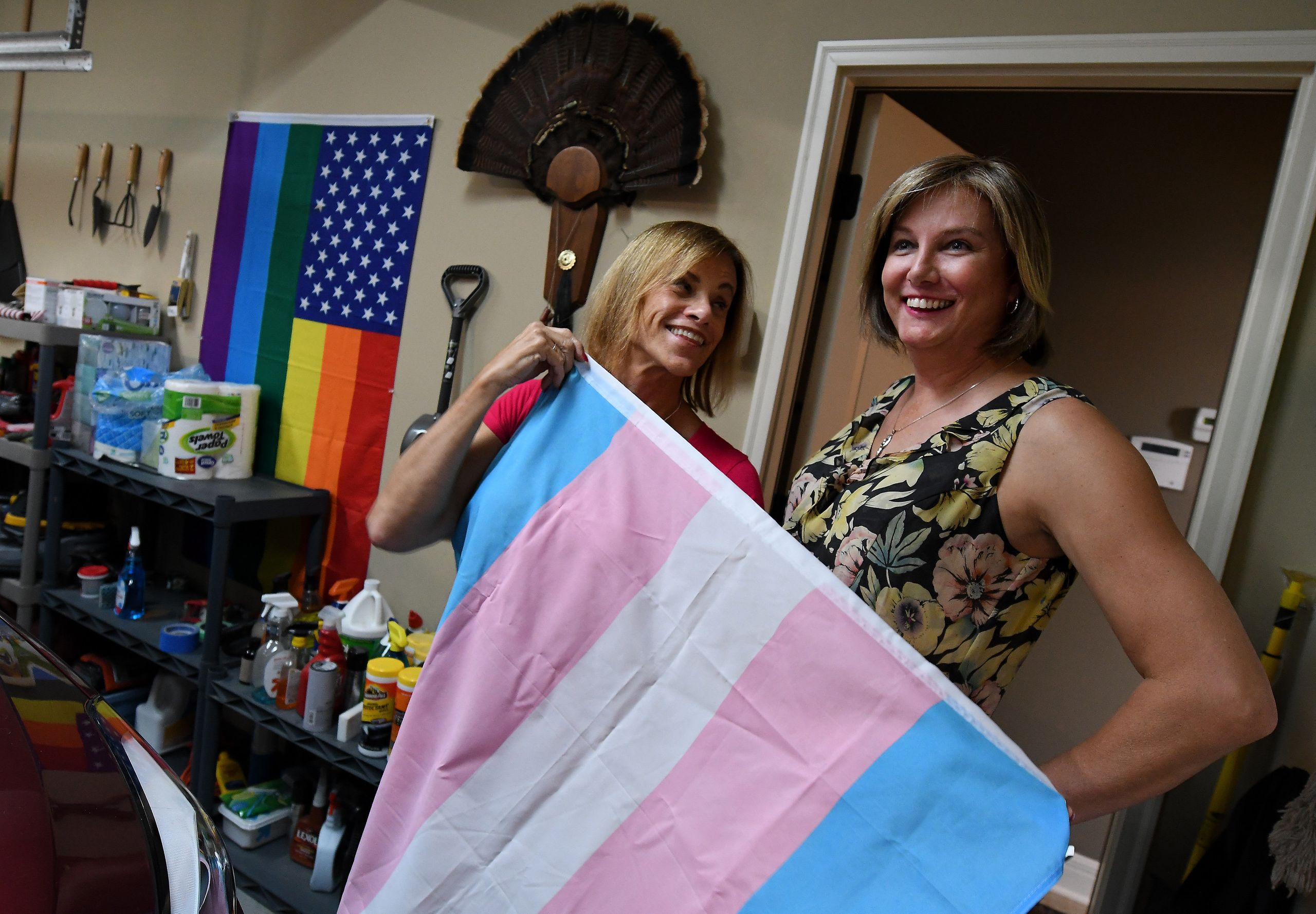 In the garage at their Shawnee home, Suzanne Wheeler and her fiancee, Marsha Riley, show off a transgender flag, wi
