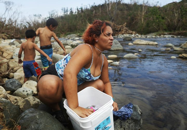 Maria Chiclano, who has no running water or power in her home, washes clothes with her sons in the Espiritu Santo river durin