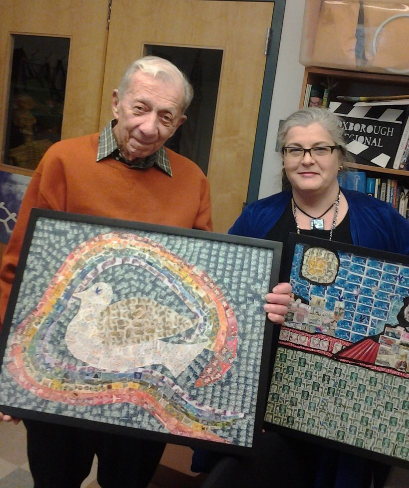 Gabriel Trost, a volunteer for the Holocaust Stamp Project, holds the <em>Dove</em>  collage, next to Jamie Droste, student l