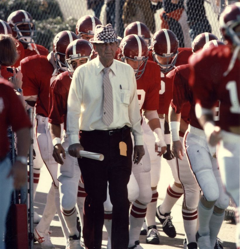 Bryant leading his team onto the field, with his trademark hat and rolled-up papers.