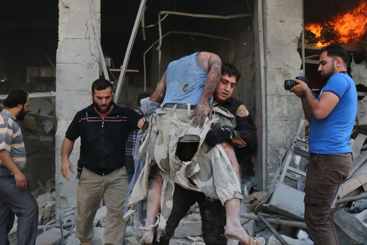 A member of the Syrian Civil Defense, also known as White Helmets, carries a victim following the airstrike at the
