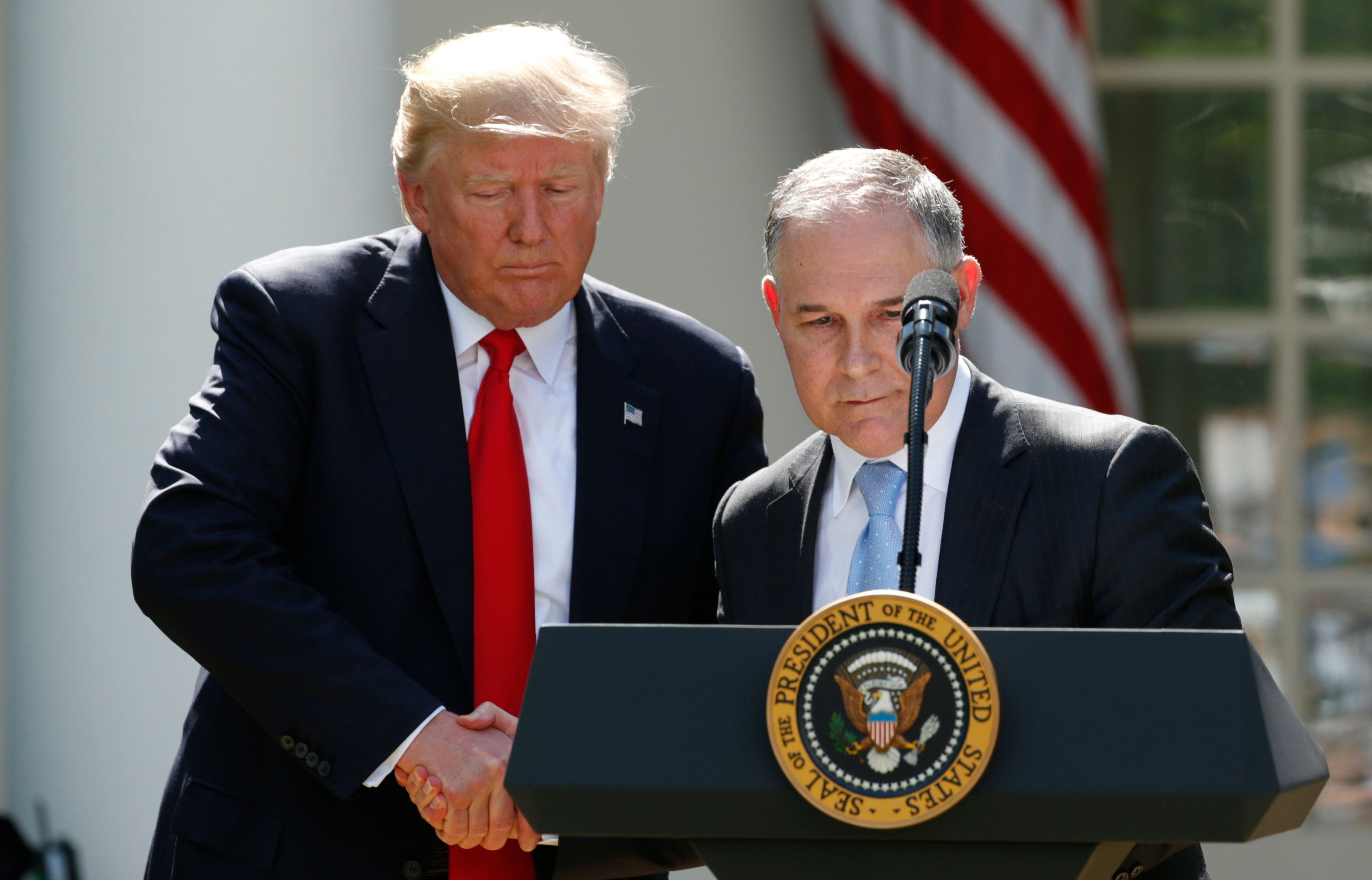 U.S. President Donald Trump (L) invites EPA Administrator Scott Pruitt to the podium after announcing his decision that the United States will withdraw from the Paris Climate Agreement, in the Rose Garden of the White House in Washington, U.S., June 1, 2017. REUTERS/Kevin Lamarque