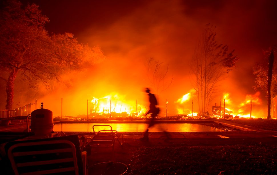 A firefighter walks near a swimming pool as a neighboring home burns.