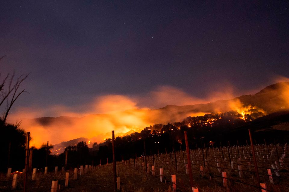Fire glows on a hillside in Napa County, California, on Oct. 9, 2017, as multiple wind-driven blazes continue to whip through