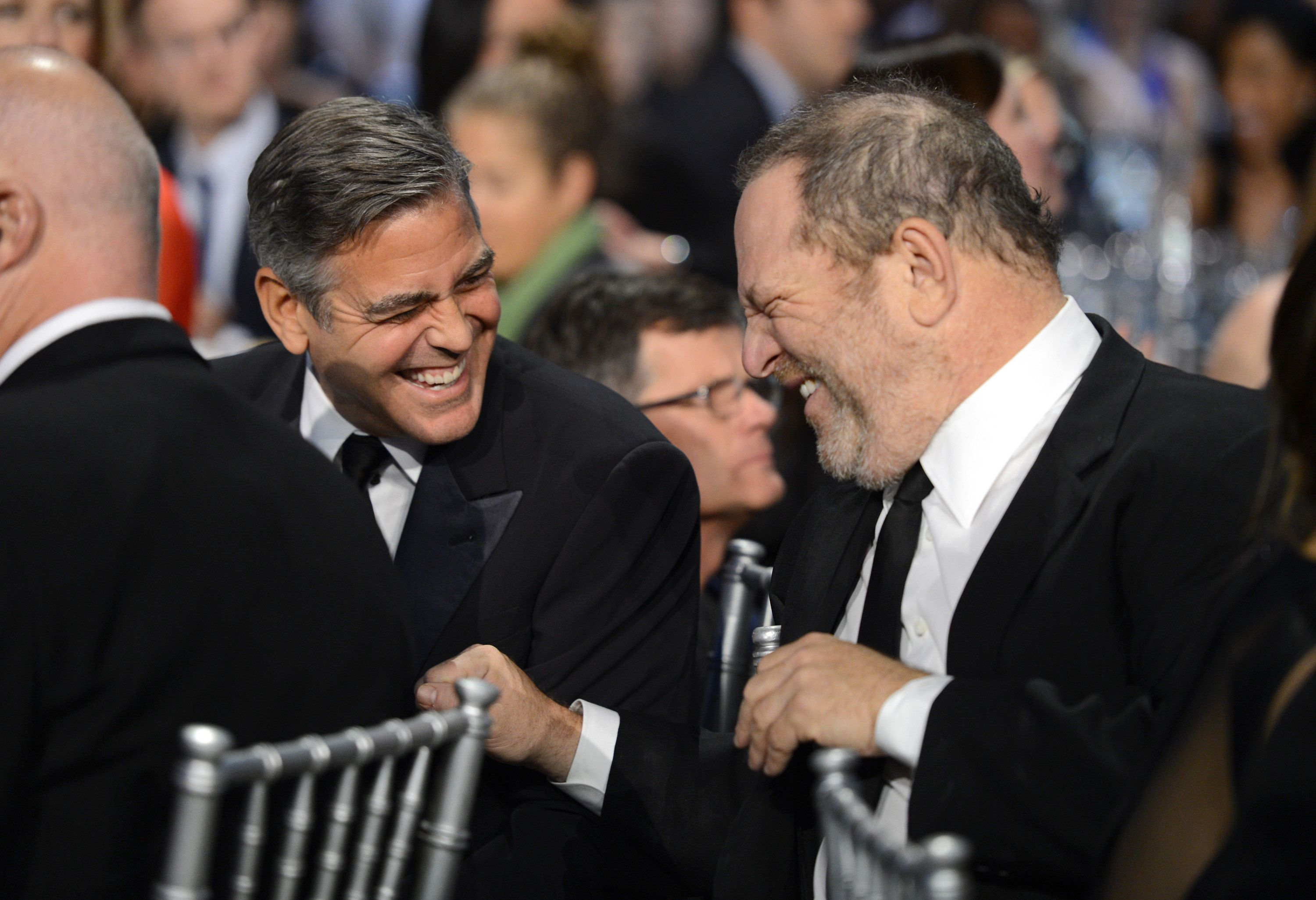 """George Clooney and Harvey Weinstein share a laugh in 2013. Clooney called the accusations against Weinstein """"disturbing"""" in p"""