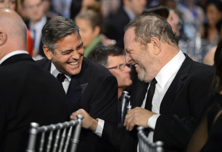"George Clooney and Harvey Weinstein share a laugh in 2013. Clooney called the accusations against Weinstein ""disturbing"" in p"