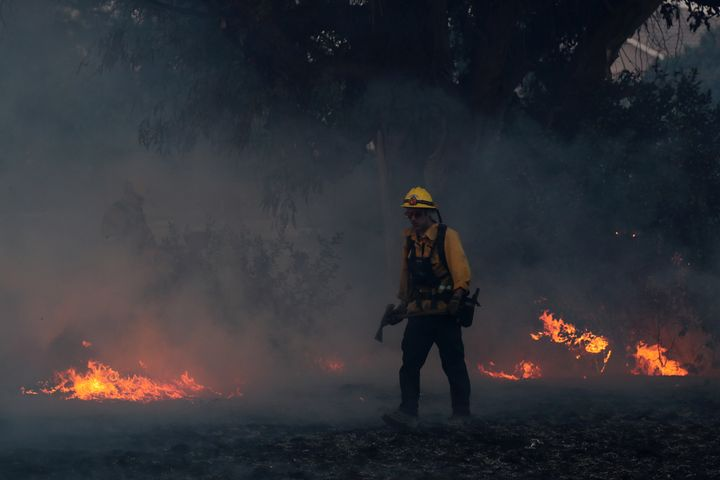A firefighter works to put out hot spots on a fast-moving, wind-driven wildfire in Orange, California.